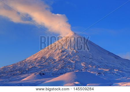 Beautiful winter volcanic landscape of Kamchatka Peninsula: view of eruption active Klyuchevskoy Volcano at sunrise. Eurasia Russia Far East Kamchatsky Region Klyuchevskaya Group of Volcanoes.
