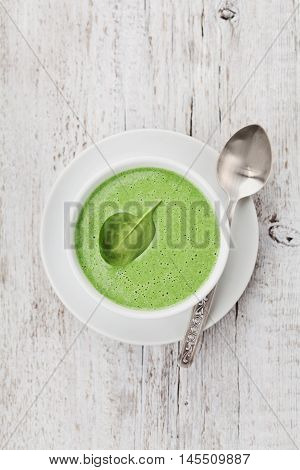 Spinach cream soup in bowl on white rustic table, top view. Copy space for text.