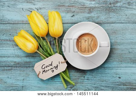 Coffee mug with yellow tulip flowers and notes good morning on blue rustic table from above. Breakfast on Mothers day or Womens day concept. poster