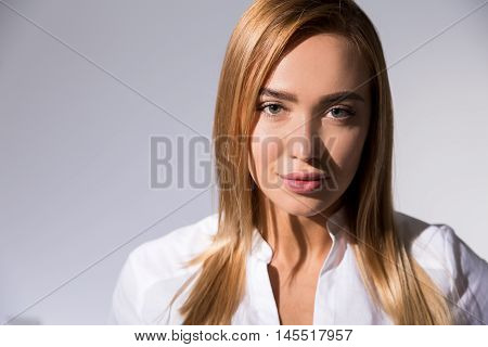 Sarcastic business woman in white shirt with long blond hair and full lips looking at viewer. Concept of intelligent office employee