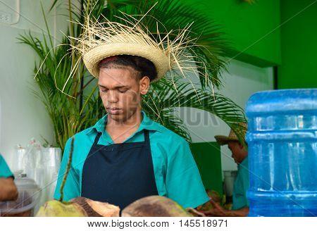 SANTO DOMINGO, DOMINICAN REPUBLIC - January 24, 2016: Barman of lemon and coconut juice, street life of Calle el Conde and Colonial Zone of Santo Domingo.