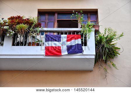 View of Calle El Conde, Count street. Dominican flag on balcony. Santo Domingo, Dominican Republic.