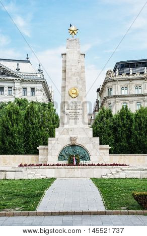 Soviet war memorial in Budapest Hungary. Cultural heritage. Architectural theme. Historical object. Travel destination. Memorial place. Vertical composition. Memorial green trees and old buildings.