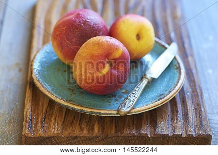 Fresh peaches in blue plate on wooden table