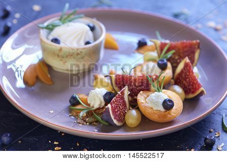 Fruit salad with homemade granola and goat cheese