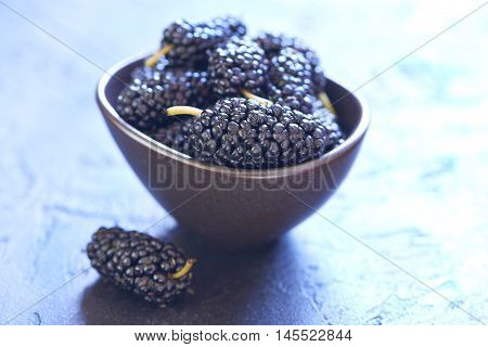 Fresh sweet mulberry in bowl on black background
