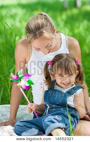 Smiling Mother And Daughter In Jeans With Colorful Toy Outdoor