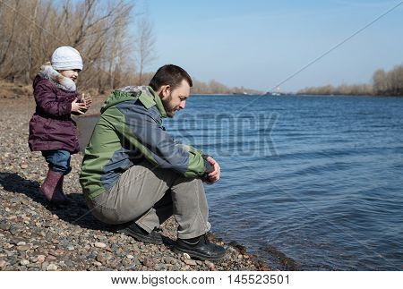 Father and daughter on a river bank. He is sitting with a sad expression, she is standing next to him.