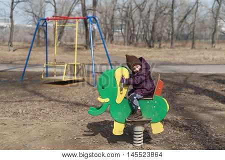 Little girl on a playground in spring time. She is sitting on an elephant. It a noon, shadows are strong.