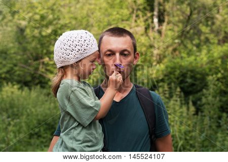 Father and daughter in the summer forest. He is holding her. She is giving him a little flower to smell.