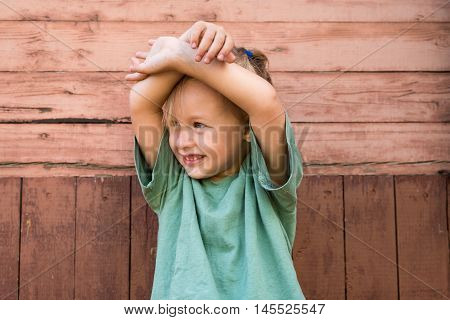 Little cute girl in front of an old wooden wall with her arms on her head. Shot with soft focus and natural lightning.