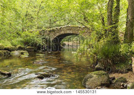 A riverside image of Hisley Bridge an old packhorse bridge over the river Bovey shot at Dartmoor Devon England UK
