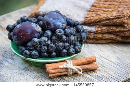 Aronia melanocarpa (Black chokeberry) and plums on wooden table. Home atmosphere. Autumn concept. Autumn harvest. Knitted things