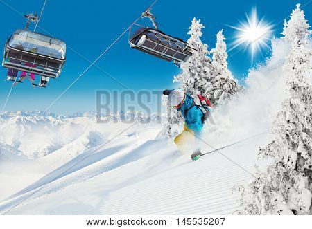 Skier on piste running downhill in beautiful Alpine landscape with ski chair lift. Blue sky on background.