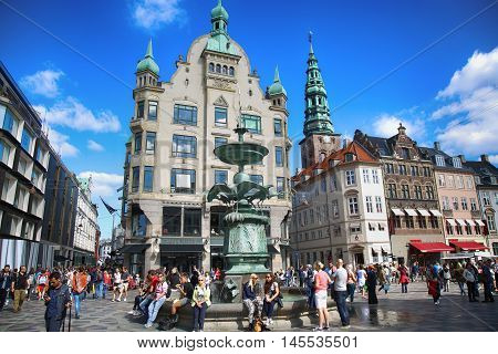 Copenhagen Denmark - August 15 2016: Many people near fountain Stork on Amagertorv square at the city centre. Copenhagen is the capital and most populated city of Denmark.
