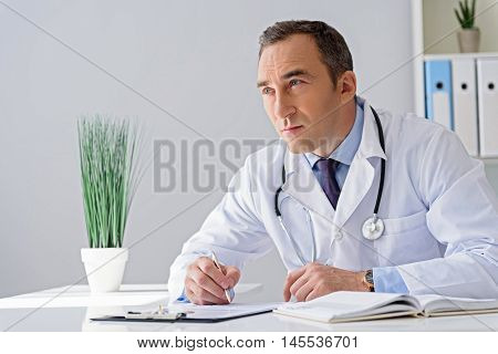 I have to think little. Handsome adult doctor sitting at table with documents and looking somewhere