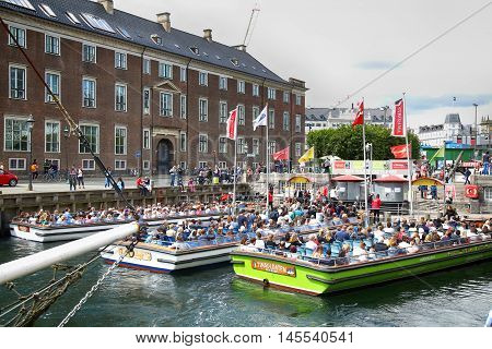 Copenhagen Denmark - August 14 2016: Tourists enjoy and sightseeing in tourist boat at the canal Nyhavn. The boat is loaded with sightseeing tourist people in Copenhagen Denmark