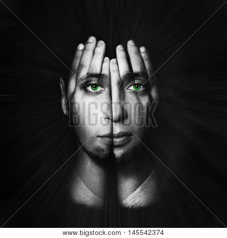 Surreal portrait of a man covering his face and eyes with his hands.Face shines through hands. Double exposure