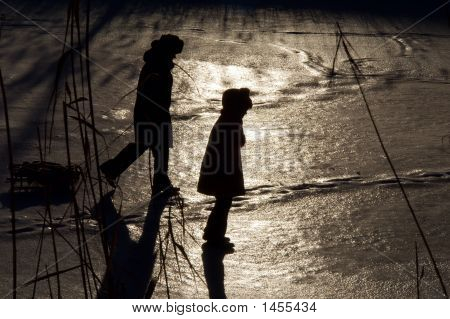 Silhouettes Of Two People On Ice Against Sun