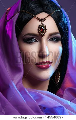 Beautiful young caucasian woman with long black hair and arabian style makeup. Vintage accessory on head. Purple fabrics. Studio shot over dark background.
