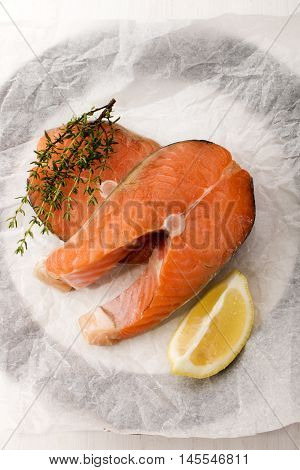 scottish salmon steak with lemon thyme and white kitchen paper on a plate