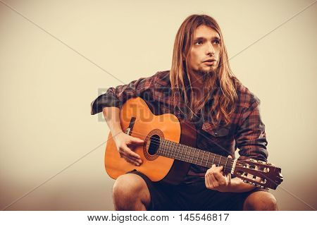 Sitting long haired bearded man playing guitar. Young male creating music. Instrument passion hobby oldschool concept.