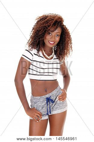 A lovely young African American woman in gray shorts and short top standing smiling isolated for white background.