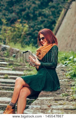 Young woman sitting and using digital tablet in the park