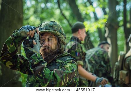 Young soldier man with beard on grime serious face in ar?y ammunition and helmet holding camera in his hands on background of soldiers in forest