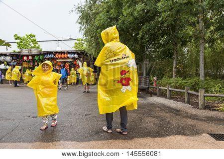 GUNZBURG GERMANY - AUG 18 2016: Family wearing yellow ponchos at the Legoland Deutschland in Guenzburg Baden Wurtemberg Germany