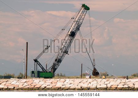 Grab crane in action to build a seawall.