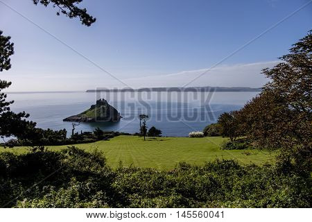 Beautiful summer scene framed by trees looking down to the Devon coast at Meadfoot Bay Torquay with Thatcher's Rock.