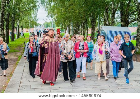 VELIKY NOVGOROD RUSSIA - AUGUST 19 2016. Theatrical excursion tour in Veliky Novgorod Russia. The guide in the character of ancient Novgorod mayor and a group of tourists at the excursion.