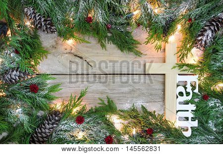 Christmas tree garland border with snow, lights, cross and the word Faith on antique rustic wooden background