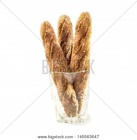 Three fresh home baked Alpine Baguettes with different cereals and seeds in glass jug isolated over white. Healthy food concept.Three fresh home baked baguettes in glass jug on white.