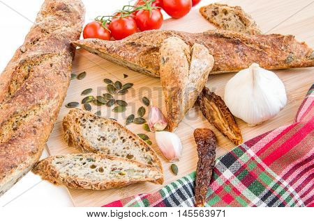 Fresh home baked Alpine Baguettes made with different cereals and seeds heart shaped slices of baguette fresh and dry tomatoes garlic and pumpkin seeds on wooden chopped board. Healthy food concept. Close-up. Top view. Horizontal.