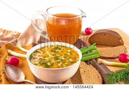 Traditional russian summer cold kvass soup okroshka in a white ceramic bowl jug with kvass (kvas) radish green onion and black rye bread on wooden cutting board. Healthy food concept. White background. Horizontal.