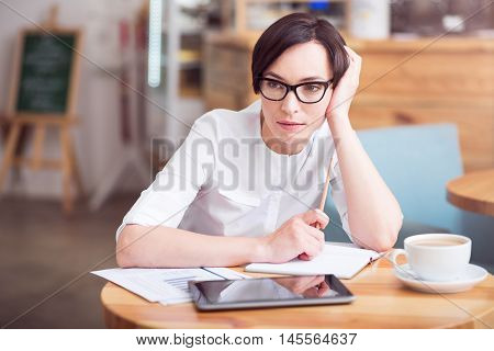 Planning. Wistful young woman sitting at the table in cafe and thinking about new steps in her own business