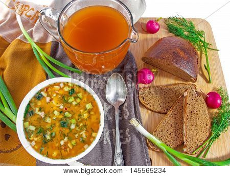 Traditional russian summer cold kvass soup okroshka in a white ceramic bowl jug with kvass (kvas) radish green onion and black rye bread on wooden cutting board. Healthy food concept. Top view. Horizontal.