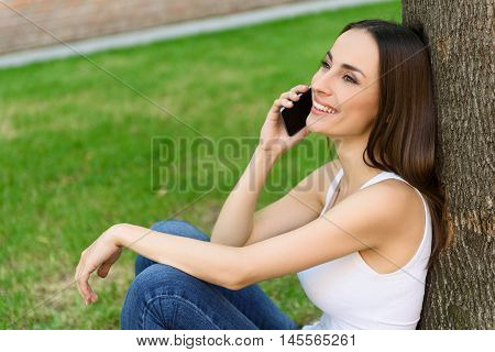 Joyful young girl is using smartphone for communication. She is sitting near tree and smiling