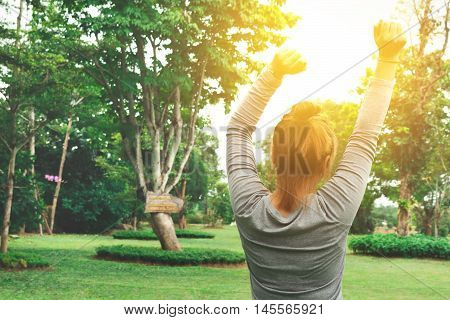 Attractive young woman enjoying her time outside in park with sunset in background.Free Happy Woman Enjoying Nature. Freedom concept. Enjoyment. soft focus.