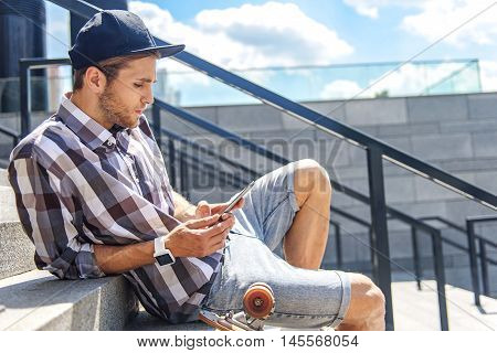 Cool young man is messaging on mobile phone with concentration. He is sitting on stairs near skate and relaxing
