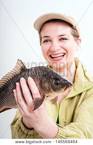 Happy woman with carp fishing trophy. Woman holding a fish