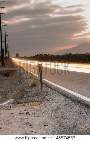 Streaking headlights down two lane rural road.