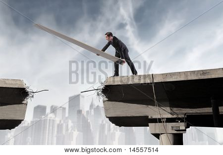 Businessman rebuilding a broken bridge