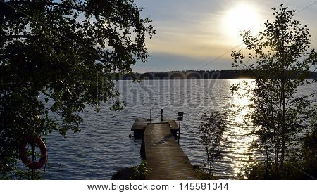 Wooden pier on the lake with wet footsteps.