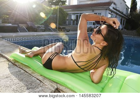 young sexy woman in bikini and sunglasses with fit beautiful body having suntan relaxing on airbed at swimming pool of vacation hotel resort in summer enjoying holidays with sun lens flare on sunset
