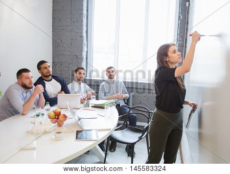 Business or freelance workshop session. Young businesswoman writing new business plan or stategy for companies, enterprises or firms while performing in board room in office.