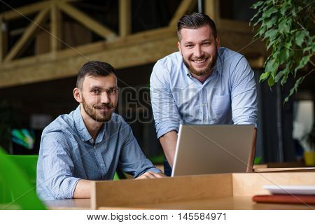 Picture of handsome businessman listening to his colleague or partner concerning ner business system while working on laptop computer in office interior.