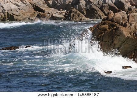 This is an image of the incoming tide hitting the rocks at the Asilomar State Preserve in Pacific Grove, California.